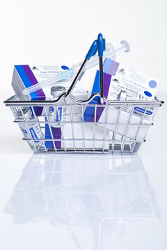 Shopping basket with Vaccine box and vial with Sputnik V vaccine Gam-COVID-Vac on white table with reflection.