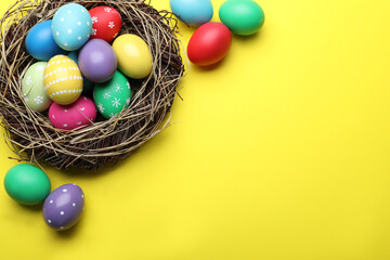 Bright painted eggs in nest on yellow background, flat lay with space for text. Happy Easter