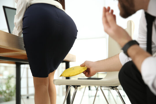 Young man putting whoopee cushion on chair while his colleague sitting down in office, closeup. Funny joke