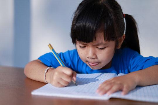 A cute little Asian girl is writing a book with a pencil on the table.