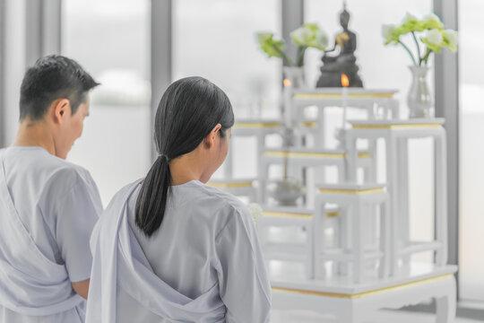 religious buddhist asian couple in white clothing worship and pray to buddha