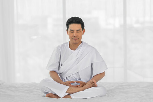religious asian man wearing white clothing having sitting meditation at home
