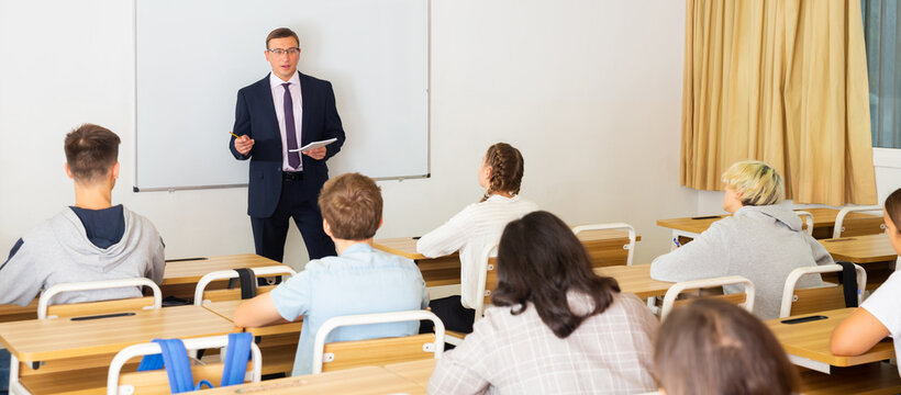 Adult teacher is giving lecture for students in the class