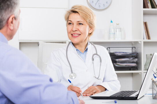 Doctor listens to mature patient and fills polling form