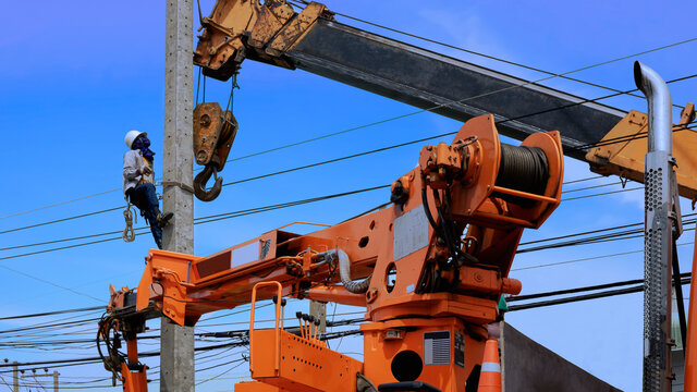 Electrical worker with crane truck working to install electric power pole on roadside against blue sky background