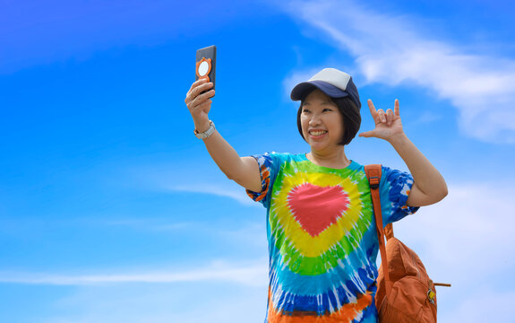 Asian fleshy female traveler in colorful casual style using smartphone taking selfie with smiling and showing love hand sign against white clouds and blue sky background