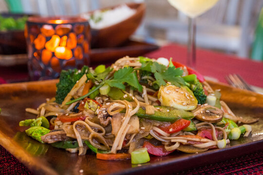 Healthy vegan Pad Thai served on a wooden plate in a relaxed environment. The meal is accompanied with a glass of white wine