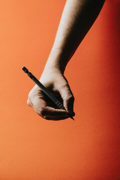 A young hand grabbing a mechanical pencil over a orange background with deep shadows