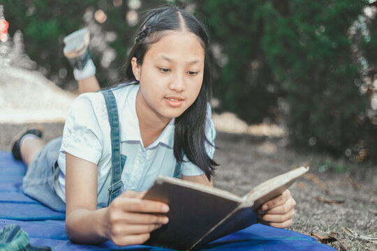 pretty teenage girl lies on meadow thinking and reading book over garden background.