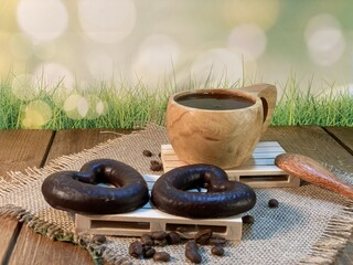 An oak table with visible grains is standing on a wood cup with black coffee. On a jute napkin, coffee beans are scattered and a gingerbread bitten heart lies on the pallet