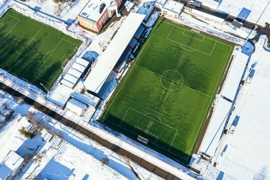 green football field and people playing football in winter stadium. birds eyes view