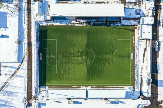 empty football or soccer stadium on a winter sunny day. aerial top view from flying drone