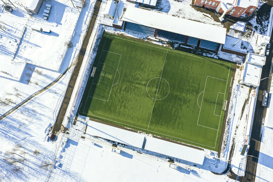 top view of empty green soccer field in winter time. drone photography