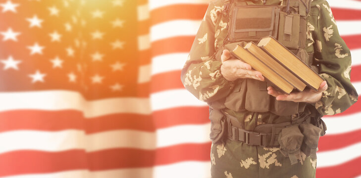 Cadet of military school with books on USA flag background .