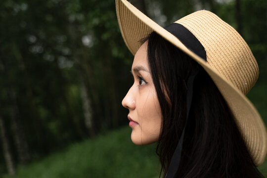 portrait of an asian girl in profile with black hair and a straw hat