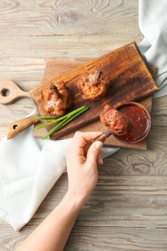 Woman eating tasty chicken lollipops with sauce on wooden background