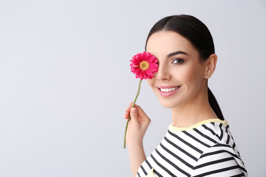 Beautiful young woman with flower on grey background