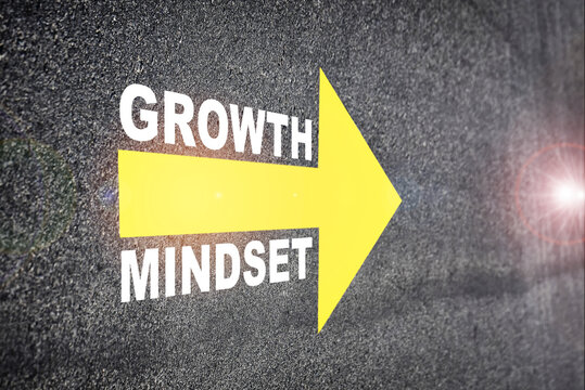 Growth mindset with yellow arrow marking on road surface. Self development to success concept and challenge idea