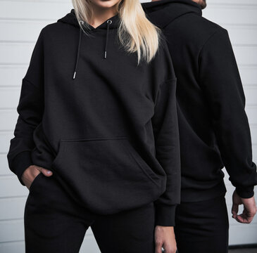 young bearded man and blonde girl is standing in plain hoodie for logo printing. Clothing mockup for hoodie. Autumn youngsters streetwear