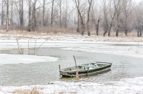 Forgotten wooden fishing boats in the frozen water of the Danube tributary, covered with snow. Vojvodina, Novi Sad, Serbia.