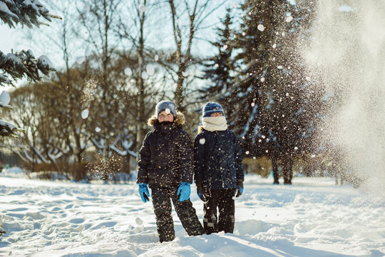 Cute caucasian boys standing under the snow squall in a snowy winter park in Russia. Image with selective focus and back light