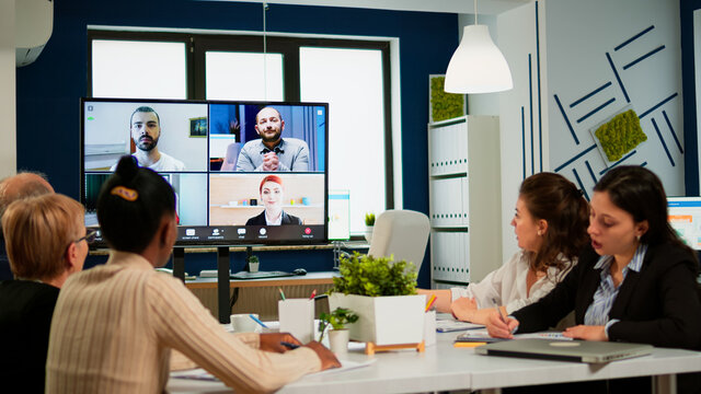 Emplyees workers having webcam group conference with coworkers speaking on video chat call with diverse colleagues online briefing. Diverse people talking at virtual meeting, online discussion.