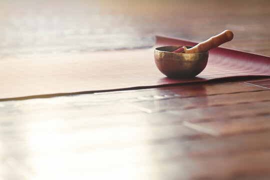 A singing bowl stands on a yoga mat on a wooden floor with copy space. Sound therapy and relaxation concept.