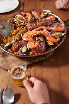 Crop friends at table with paella dish