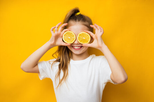 Little smiling cute blond girl in yellow t-shirt holding halves of fresh sour lemon fruit near eyes and showing tongue over yellow background. Healthy lifestyle and clean eating concept