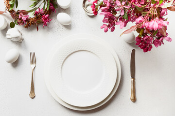 Festive Easter table setting with blooming apple flowers on white table. Top view. Elegance dinner.