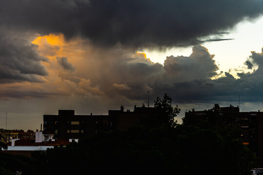 Beautiful dramatic stormy clouds at sunset over silhouette of the city. Cumulonimbus cloud