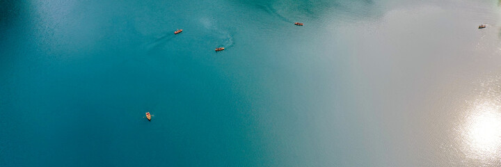 Boats from the air. Aerial view of a lake in Italy. Summer landscape with clear water on a sunny day. Top view of the boat from a drone. The clouds are reflected in the water