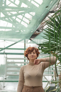 A beautiful plus size girl enjoying standing among the green plants of the greenhouse. Cottagecore style
