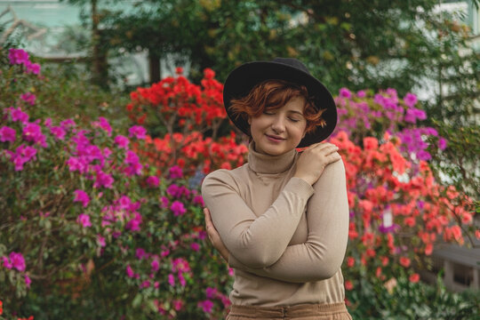 A beautiful plus size girl in a hat hug herself enjoying standing among the green plants of the greenhouse. Cottagecore style. Self love concept