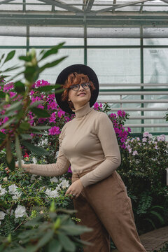 A beautiful plus size girl in a hat and glasses smiles among the green plants of the greenhouse. Cottagecore style
