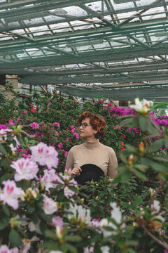 A beautiful plus size young woman standing among the green plants of the greenhouse. Cottagecore style with bright flowers