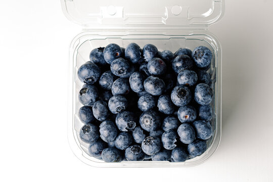 transparent blueberry jar, on white background, with open lid, viewed from above, horizontal format