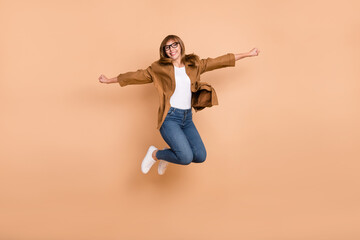 Wall Mural - Full body photo of happy nice woman jump up air good mood smile isolated on pastel beige color background