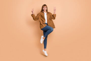 Wall Mural - Full length photo of happy charming young woman make v-signs jump up isolated on pastel beige color background