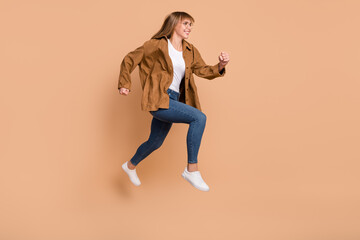 Wall Mural - Full body profile side photo of young charming lady jump up run sale empty space isolated on beige color background