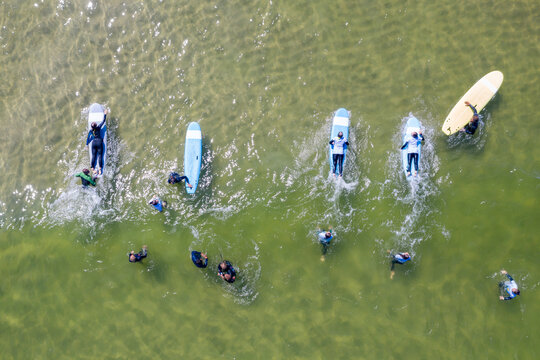 Aerial drone view of people surfing in the sea. Summer sport learning how to surf. Surfboarding in baltic sea Jastarnia, Poland