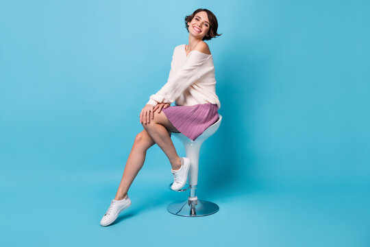 Photo portrait full body view of gorgeous woman sitting on bar stool isolated on pastel blue colored background