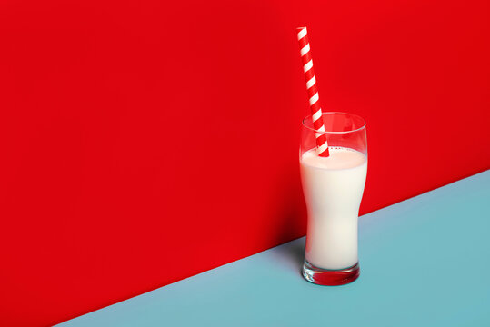 Glass of milk and a red and white drinking straw