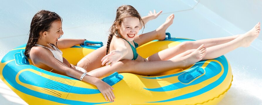 Two little girls on tube on water slide at aquapark. Summertime, vacation, entertainment, childhood concept. Colorful banner.