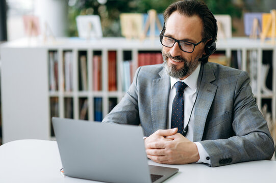Happy caucasian businessman at video conference, talking with colleagues about work process. Stylish mature manager in headset and eyeglasses is using laptop, sitting at the desk, smiling