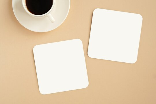 Two white coasters mockup for design presentation, top view on table with coffee cup.