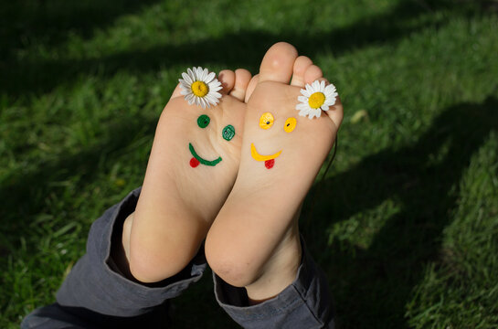 smiling faces are painted on the bare feet of a child lying on green grass on a sunny day. Chamomile flowers between fingers, cheerful positive atmosphere, happy childhood. Hi summer, smile day