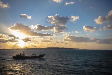 바다를 가로지르는 배와 황금빛 석양 Fotobehang