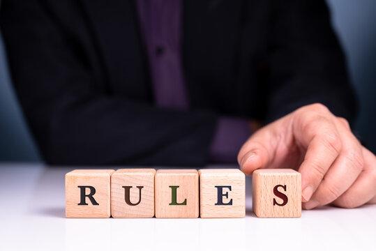 Businessman arrange the wood blocks of RULES word