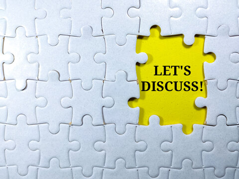 Selective focus.Word LET'S DISCUSS with jigsaw puzzle on yellow background.Business concept.